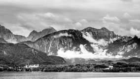 Lake forggen, füssen and alps. Black & white landscape from lake forggen over füssen and allgäu woods to some alp mountains royalty free stock images