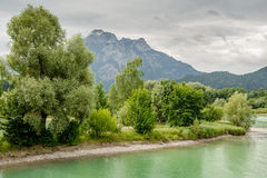 Lake forggen. Landscape from lake forggen over woods to alp mountain stock photos