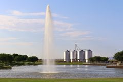 Lake with Fountain and Silos in the Background. Four silos behind a lake with a fountain Royalty Free Stock Photo