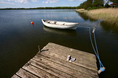 Lake fun. A lake in denmark with child playing on a wooden bridge and boat - in denmark Stock Photography