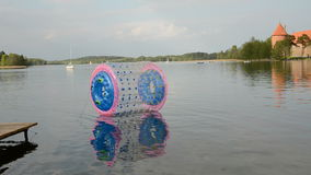 Lake Galve with zorbing ball and Trakai castle. Lithuania stock video footage