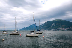 Lake Garda in the early morning, Italy. Moored yachts on the smooth surface of lake Garda in the early morning, Italy Royalty Free Stock Photography