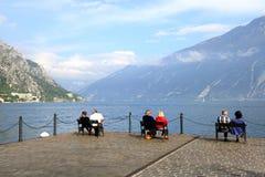 Lake Garda. GARDA,ITALY- OCTOBER 12, 2014: Tourist sitting on a pier of Garda lake, Italy.Garda is a comune on the shore of Lake Garda, in the province of Verona Royalty Free Stock Image