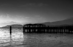 Lake Garda. Old pier stretching out over Lake Garda, Italy with water and mountains in the distance royalty free stock image