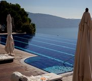 Lake Garda lake view of Alps and Lake. A beautiful vanishing edge swimming pool seems to vanish into Lake Garda far below in Italys lake district on a warm Royalty Free Stock Photo