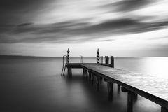 Lake Gardasee in Northern Italy, black and white shot. Jetty at lake Gardasee in Northern Italy, Europe, black and white long time exposure Royalty Free Stock Photo