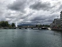 Lake Genève. Clouds, fountain, ferriswheel, lake, water, houses, mountain Stock Photos