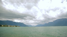 Lake Geneva, a picturesque pond between high mountains, floating boat. Lake Geneva on the north side of the Alps, shared between Switzerland and France. It is stock footage