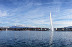 Lake Geneva Switzerland with water fountain and blue sky with cl. Horizontal image of Lake Geneva, Switzerland, with famous Jet d Eau fountain in background on stock photos