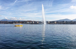 Lake Geneva Switzerland with water fountain and water taxi on a. Horizontal image of Lake Geneva, Switzerland, with famous Jet d Eau fountain in background on royalty free stock photos