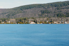 Lake George Winter. Color DSLR stock image of a frozen Lake George, New York, with lake houses on the shore and Adirondack Mountains in background. Horizontal Stock Images