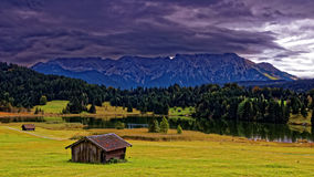 Alpine landscape and lake by storm clouds. Autumnal scenery in the Bavarian Alps, Germany, with its characteristic wooden sheds. A massive mountain range in the Royalty Free Stock Photo
