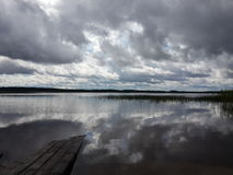 Lake with grass and rainy clouds.  Royalty Free Stock Photo