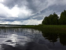 Lake with grass and rainy clouds Stock Image