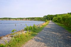 Lake and Gravel Road. The shoreline of a reservoir or lake with a gravel road at the border Stock Photos