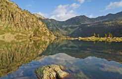 Lake in great Pyrenees mountains. Just after sunrise, summits reflects in the translucent and peaceful water, a rock with grass in foreground, and small island Royalty Free Stock Image