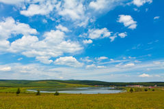 Lake and green grass under the blue sky and white clouds Royalty Free Stock Photos