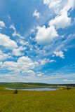 Lake and green grass under the blue sky and white clouds Stock Photo