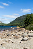 Lake and Green Hill Past Rocky Beach Royalty Free Stock Photography