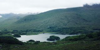 Lake and green hills. Kerry Mountains landscape. Lake and green hills. A scenic view of a Kerry Mountains and surrounding areas in County Kerry. Aged effect stock photo