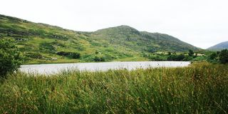 Lake and green hills. Kerry Mountains landscape. Lake and green hills. A scenic view of a Kerry Mountains and surrounding areas in County Kerry. Aged effect stock image