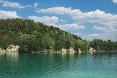 Lake with green water and hill with trees Royalty Free Stock Images