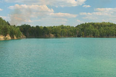 Lake with green water and trees, smoke Royalty Free Stock Photos