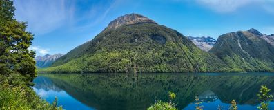 Lake Gunn Panorama with Reflections in Water. Scenic stopover on the road to Milford Sound in Fiordland National Park, New Zealand, South Island Royalty Free Stock Image
