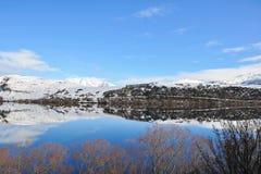 Lake Hayes med snowbergreflexioner Arkivbilder