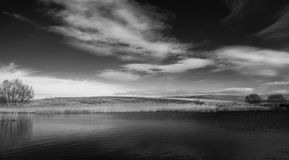 Lake in the hills panorama in black and white Royalty Free Stock Photos