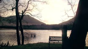Lake in the hills. Sun setting behind a hill in the west of Ireland royalty free stock photos