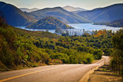 Lake Hodges and Back Road, California. A back road winds through trees and bushes downhill at the edge of a misty, glistening reservoir known as Lake Hodges in royalty free stock photo