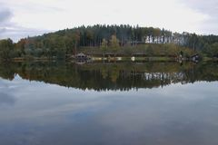 Lake Hollerersee, a small moorland lake in Upper Austria, in autumn. Forest and buildings reflect in the dark water. Haigermoos, Austria, Europe stock image