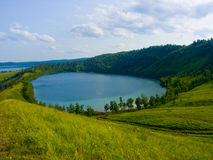 Lake in a hollow of a hill. The image of the lake located in a hollow of a hill Royalty Free Stock Photography