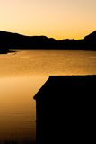 Lake House. A boat shed silhouette at sunrise at Llyn Ogwen, Wales Stock Image