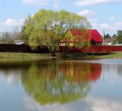 Lake house. A view of a house and a tree on a lake Royalty Free Stock Image