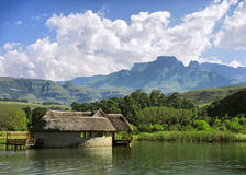 Lake house against mountains and Cathkin peak Royalty Free Stock Image