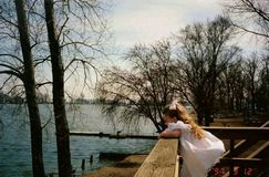 Lake house. Country girl at the lake in her fancy white dress Stock Photography