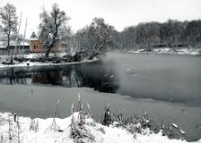 Lake house. Forest. Bare branches of trees. First snow. Dark leaden water. Dry grass. Grey sky Stock Images