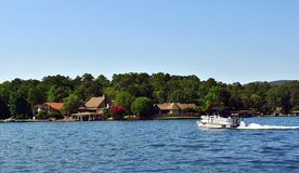 Lake House on the Lake with a Pontoon Boat in the Water. Beautiful scenic view of lake houses on the shoreline with a pontoon boat in the water royalty free stock photo