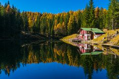 Lake house reflecting in calm waters Stock Images