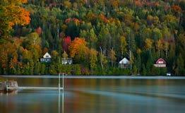 Lake houses line a Vermont pond in peak autumn stock photo