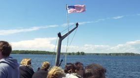 Tourists Sailing on a Boat with an American Flag. Lake Huron, Ontario, Canada. June 1st, 2017. The American flag flaps in the wind above a clear blue sky as stock video footage