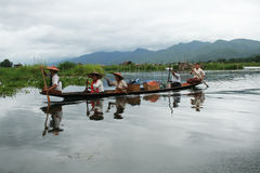 Lake inle. A boat with five women is sailing on the lake inle in myanmar.they are going back from the market.august 2007 Stock Photo