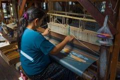 A Burmese woman weaves a fabric. Myanmar Burma. LAKE INLE, MYANMAR - DECEMBER 26, 2016: A Burmese woman weaves a fabric on a loom from aquatic plant fibers stock photo