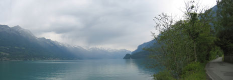 Lake Interlaken. And a shore road with the Alps mountains in the backgound - Switzerland - Panorama Royalty Free Stock Photos