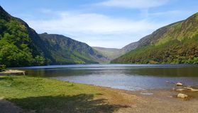 Lake in irish mountains with blue sky and forest in background. Stock Photography