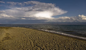 Lake Issyk-Kul in Kyrgyzstan at sunset. Lake Issyk-Kul in Kyrgyzstan, at sunset, the waves on the lake, a turquoise lake, clouds on the sky Stock Photography