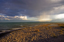 Lake Issyk-Kul in Kyrgyzstan at sunset. Lake Issyk-Kul in Kyrgyzstan, at sunset, the waves on the lake, a turquoise lake, clouds on the sky Stock Image