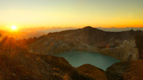 Lake in the Kelimutu volcano in Indonesia in the morning at sunrise. High panoramic view of the green turquoise colored lake in the Kelimutu volcano during the Stock Photography
